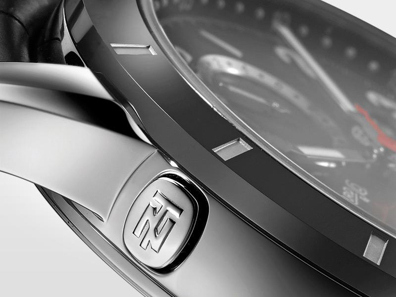 Un discreto pulsador de forma alargada activa, la nueva función de doble huso horario. Diseño sencillo y funcional.