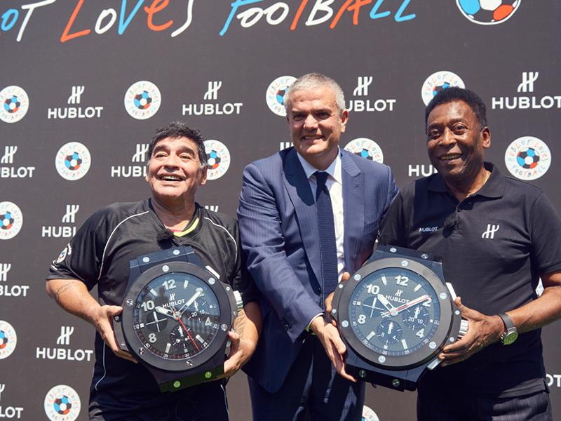 Maradona, Ricardo Guadalupe y Pelé sostienen los tableros electrónicos que usa el cuarto árbitro para anunciar los cambios y el tiempo añadido.